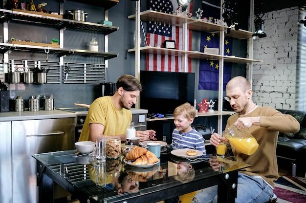 Молодой человек кормит сына завтраком, когда его муж наливает свежий апельсиновый сок в очки