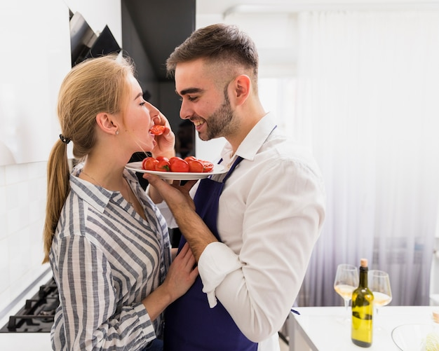 Young man feeding woman with tomatoes
