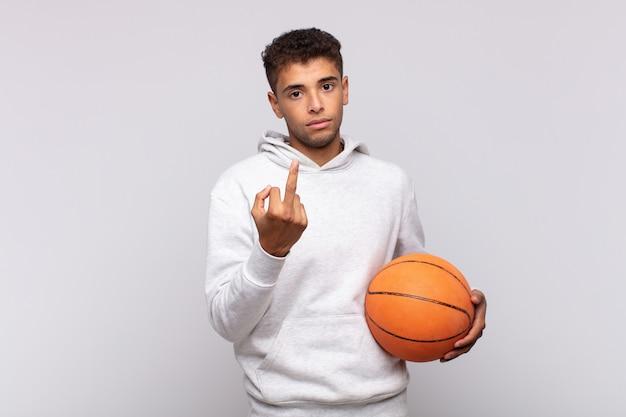 若い男は怒り、イライラ、反抗的、攻撃的で、中指をひっくり返し、反撃しました。バスケットコンセプト