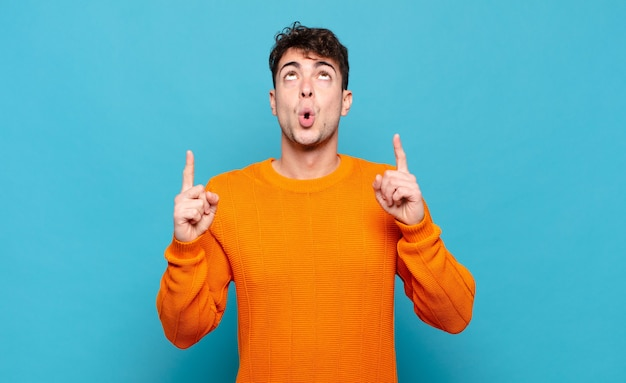 Young man feeling awed and open mouthed pointing upwards with a shocked and surprised look