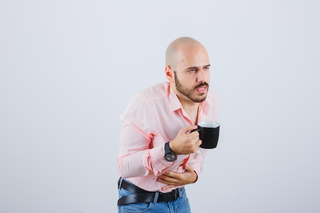 Young man feeling bad after drinking in pink shirt,jeans and looking troubled. front view.