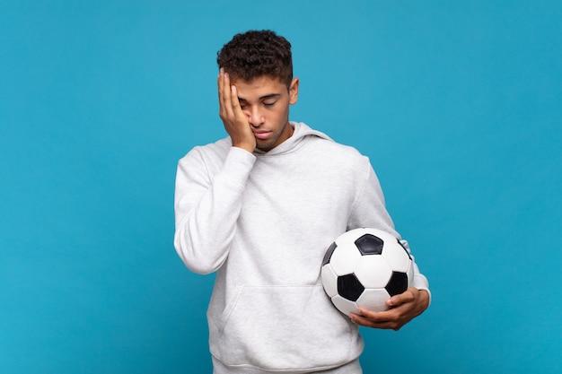 Молодой человек чувствует скуку, разочарование и сонливость после утомительной, скучной и утомительной работы, держа лицо рукой. футбольная концепция