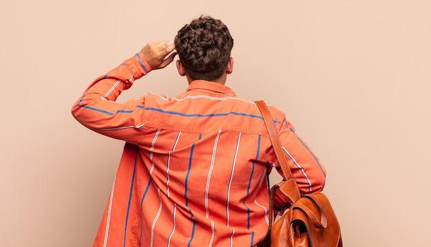 若い男は無知で混乱していると感じ、解決策を考え、腰に手を、頭に他の手を、背面図で。学生の概念