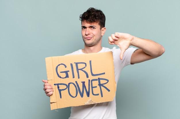 Молодой человек чувствует раздражение, злость, раздражение, разочарование или недовольство, показывая большой палец вниз серьезным взглядом