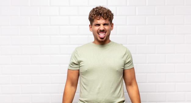 若い男は嫌悪感とイライラを感じ、舌を突き出し、厄介で厄介なものを嫌います