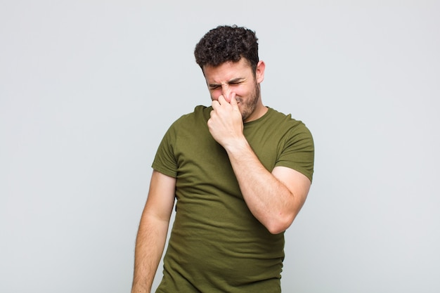 Young man feeling disgusted, holding nose to avoid smelling a foul and unpleasant stench