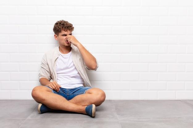 嫌悪感と不快な悪臭を嗅ぐのを避けるために鼻を保持している若い男