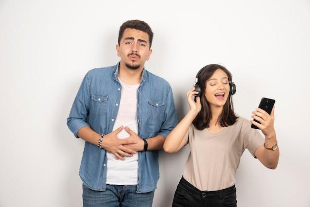 女性が歌を歌っている間、若い男性は落ち込んでいます。