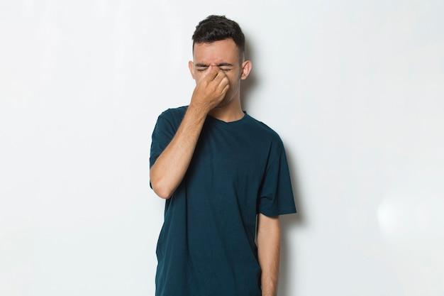 Young man feeling eye pain isolated on white background