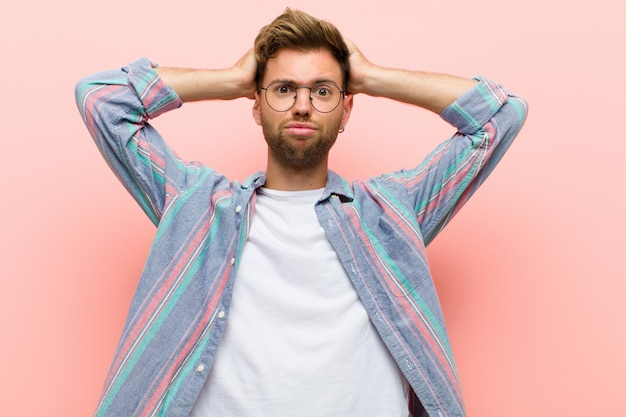 Young man feeling frustrated and annoyed, sick and tired of failure, fed-up with dull, boring tasks against pink background