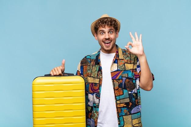 若い男は幸せ、驚き、満足、驚きを感じ、大丈夫と親指を立てるジェスチャーを示し、笑顔