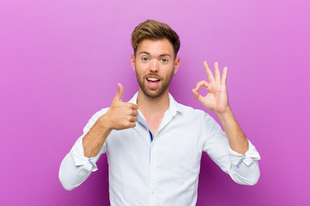 Young man feeling happy, amazed, satisfied and surprised, showing okay and thumbs up gestures, smiling over purple wall