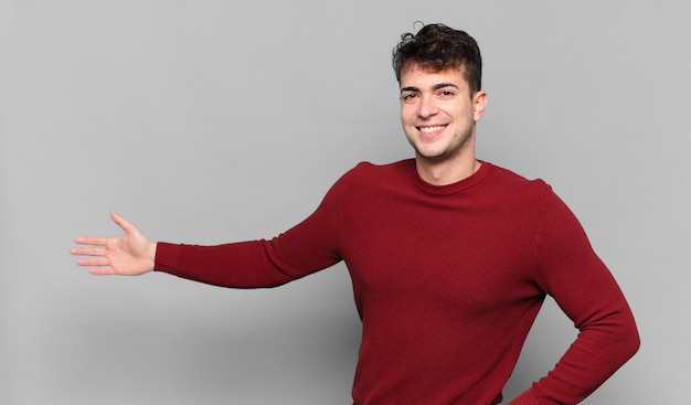 행복하고 쾌활한 느낌, 미소 짓고 환영하는 청년, 친절한 제스처로 당신을 초대합니다.