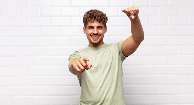 Young man feeling happy and confident, pointing at front with both hands and laughing, choosing you
