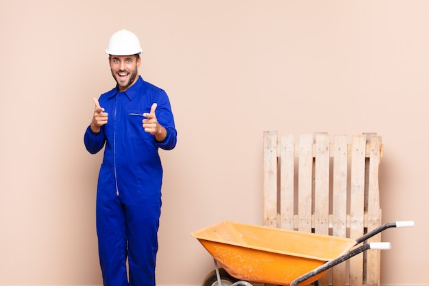 Young man feeling happy, cool, satisfied, relaxed and successful, pointing at camera, choosing you construction concept
