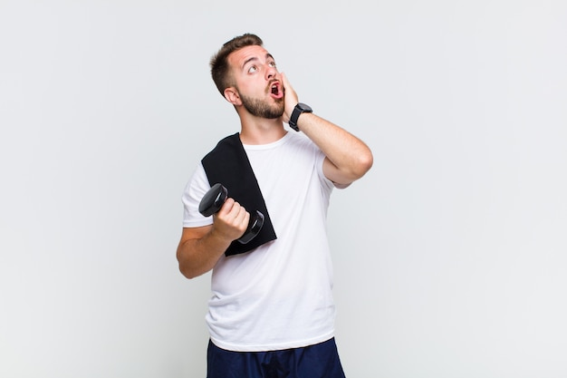 Young man feeling happy, excited and surprised, looking to the side with both hands on face