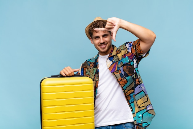Young man feeling happy, friendly and positive, smiling and making a portrait or photo frame with hands. holidays concept