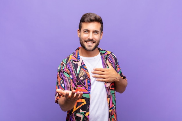 Young man feeling happy and in love, smiling with one hand next to heart and the other stretched up front