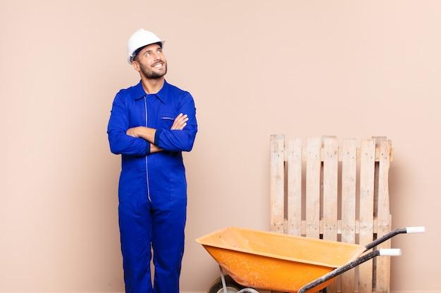 幸せ、誇り、希望を感じ、不思議に思ったり、考えたり、交差した腕の建設コンセプトでスペースをコピーすることを見上げている若い男