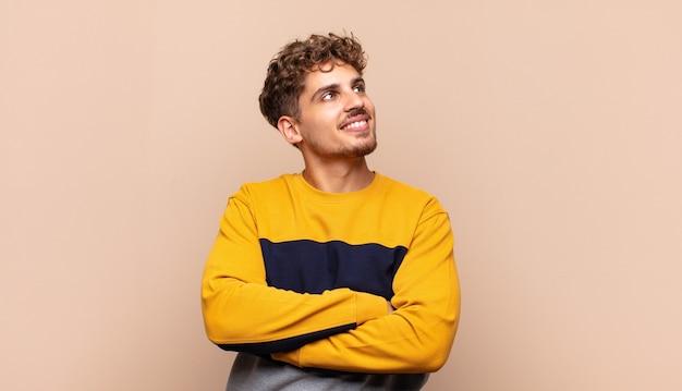 Молодой человек чувствует себя счастливым, гордым и обнадеживающим, задается вопросом или думает, смотрит вверх, чтобы скопировать пространство со скрещенными руками