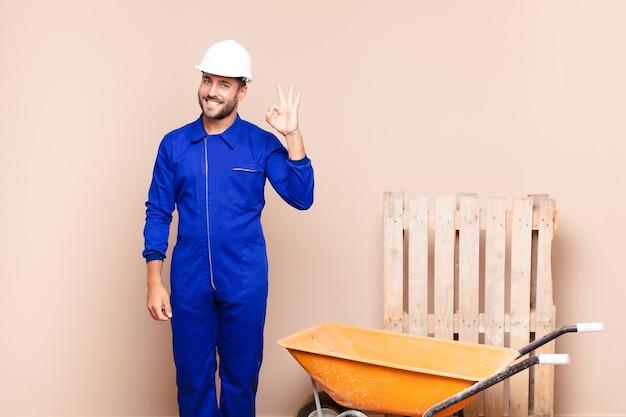 젊은 남자는 행복하고 편안하며 만족하며 괜찮은 제스처, 웃는 건설 개념으로 승인을 보여줍니다.