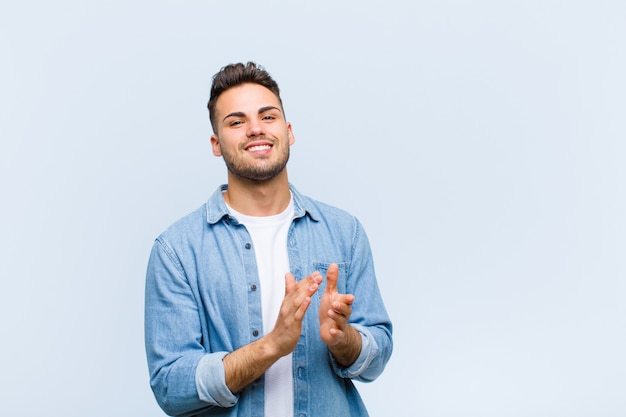 Young man feeling happy and successful, smiling and clapping hands, saying congratulations with an applause over blue wall
