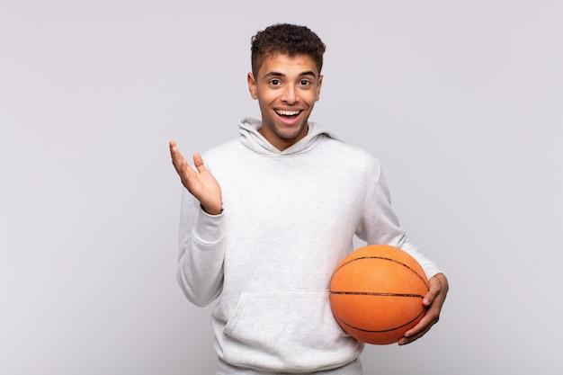 幸せ、驚き、陽気を感じ、前向きな姿勢で笑顔で、解決策やアイデアを実現する若い男。バスケットコンセプト