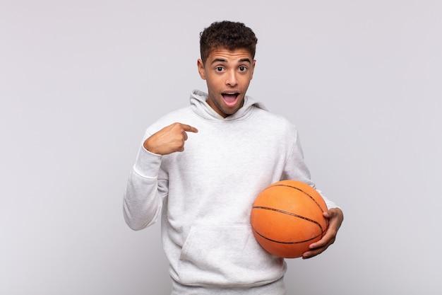 若い男は幸せ、驚き、誇りを感じ、興奮した、驚いた表情で自分を指しています。バスケットコンセプト