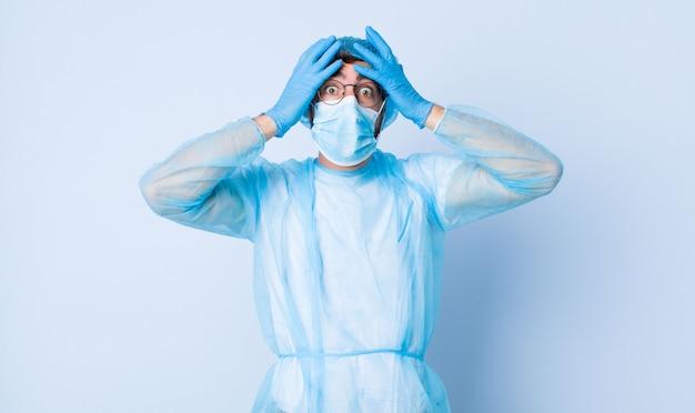 젊은이는 충격을 받고 머리에 손을 들고 실수에 당황했습니다. 코로나 바이러스 개념