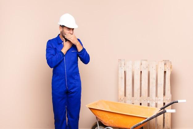 Молодой человек чувствует себя плохо с симптомами боли в горле и гриппа, кашляет с закрытым ртом строительной концепцией