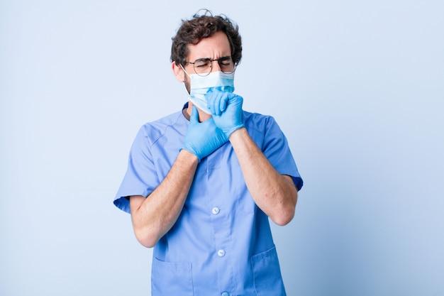 若い男は喉の痛みやインフルエンザの症状で気分が悪くなり、口を覆ったまま咳をします。コロナウイルスの概念
