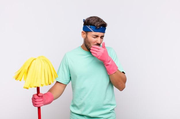 喉の痛みとインフルエンザの症状で気分が悪くなり、口を覆って咳をする若い男性