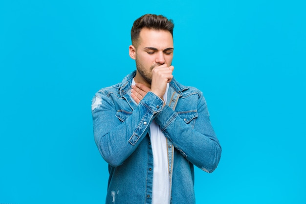 Young man feeling ill with a sore throat and flu symptoms, coughing with mouth covered over blue wall