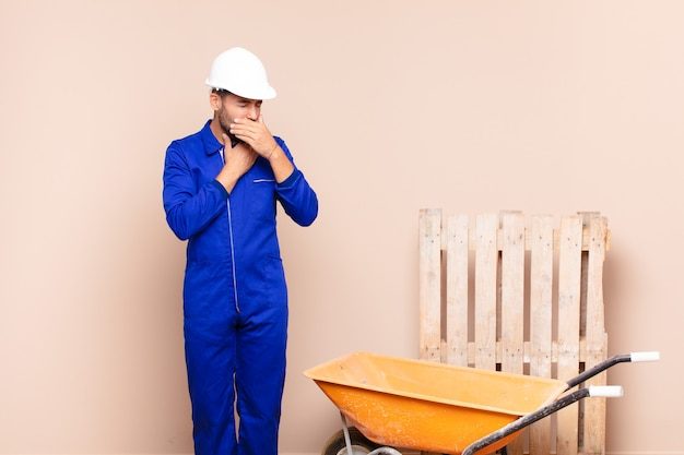 Young man feeling ill with a sore throat and flu symptoms, coughing with mouth covered construction concept