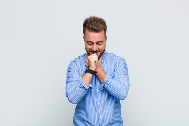 Young man feeling ill with a sore throat and flu symptoms, coughing with mouth covered