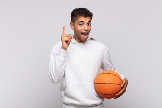 アイデアを実現した後、元気に指を上げて幸せで興奮した天才のように感じる青年、エウレカ!バスケットコンセプト