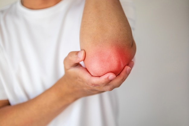 Young man feeling pain in elbow healthcare concept