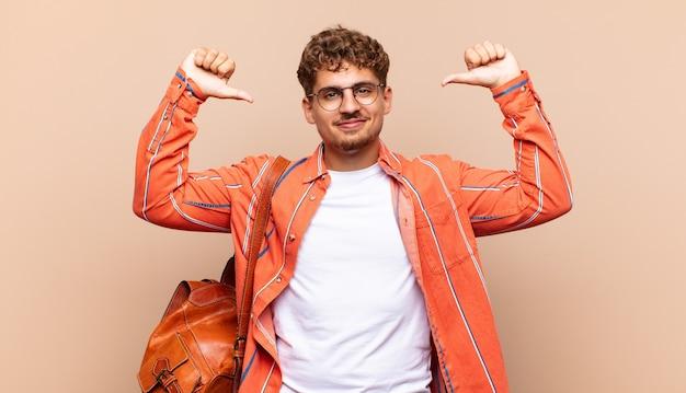 Молодой человек чувствует себя гордым, высокомерным и уверенным, выглядит довольным и успешным, указывая на себя. студенческая концепция