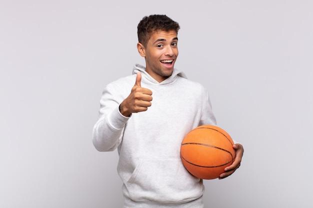 若い男は、誇りを持って、のんきで、自信を持って、幸せを感じ、親指を立てて前向きに笑っています。バスケットコンセプト