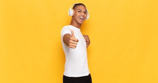 若い男は、誇り、のんき、自信を持って幸せを感じ、親指を立てて前向きに笑っています