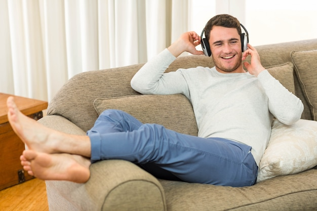 Young man feeling relaxed while listening to music with headphones in living room