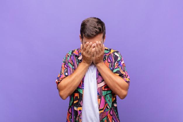 Молодой человек грустит, разочарован, нервничает и подавлен, закрывает лицо обеими руками, плачет