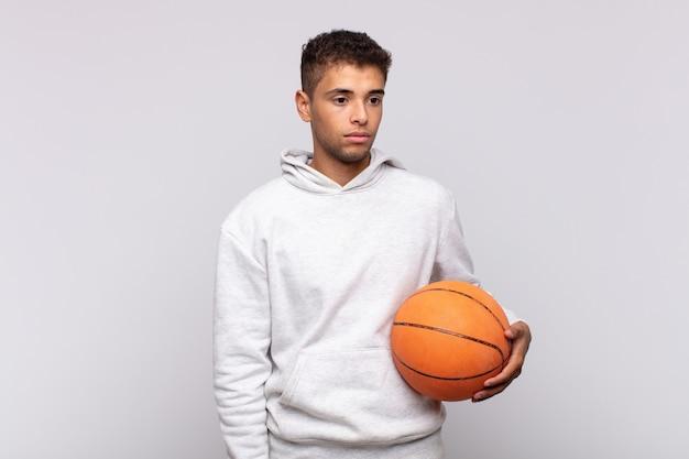 若い男は、悲しみ、動揺、または怒りを感じ、否定的な態度で横を向いて、意見の相違に眉をひそめています。バスケットコンセプト