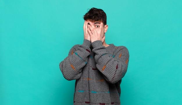 Молодой человек чувствует себя напуганным или смущенным, подглядывает или шпионит глазами, наполовину прикрытыми руками
