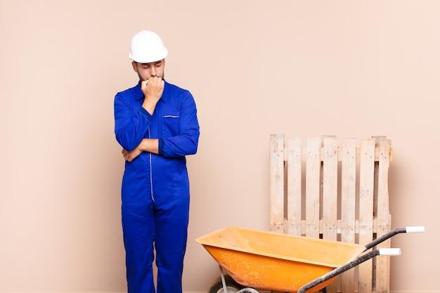 턱 건설 개념에 대해 누르면 손으로 옆으로 쳐다보고 진지하고 사려 깊고 걱정되는 젊은 남자
