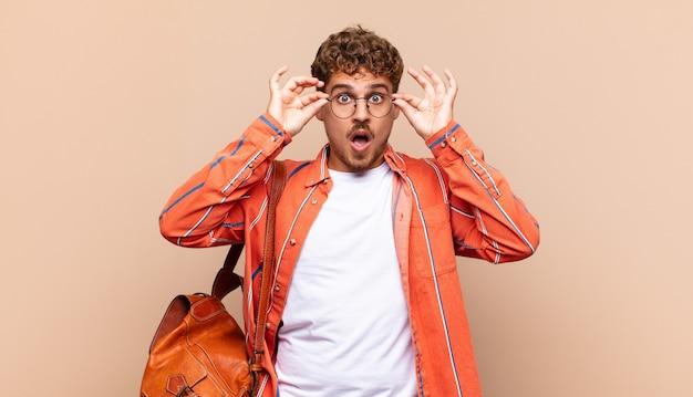 Молодой человек чувствует себя потрясенным, изумленным и удивленным, держит очки с удивленным, недоверчивым взглядом. студенческая концепция