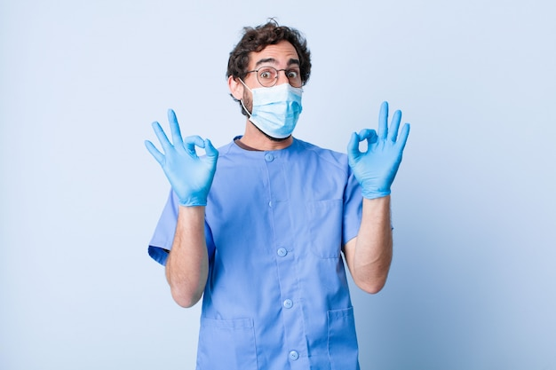 Young man feeling shocked, amazed and surprised, showing approval making okay sign with both hands. coronavirus concept