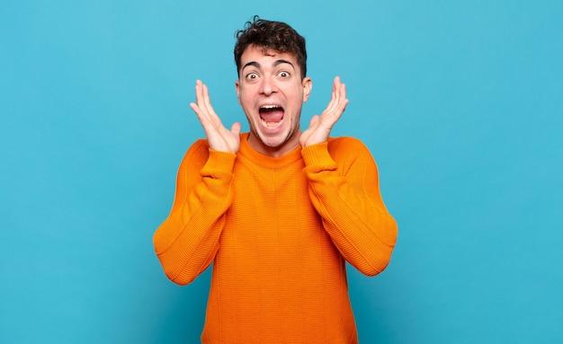 Молодой человек чувствует себя потрясенным и взволнованным, смеющимся, удивленным и счастливым из-за неожиданного сюрприза