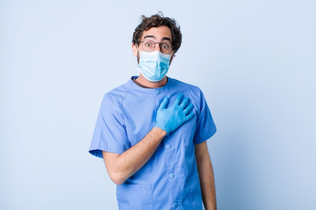 Молодой человек чувствует себя шокирован и удивлен, улыбаясь, принимая руку к сердцу, счастлив быть тем или показывая благодарность. концепция коронавируса
