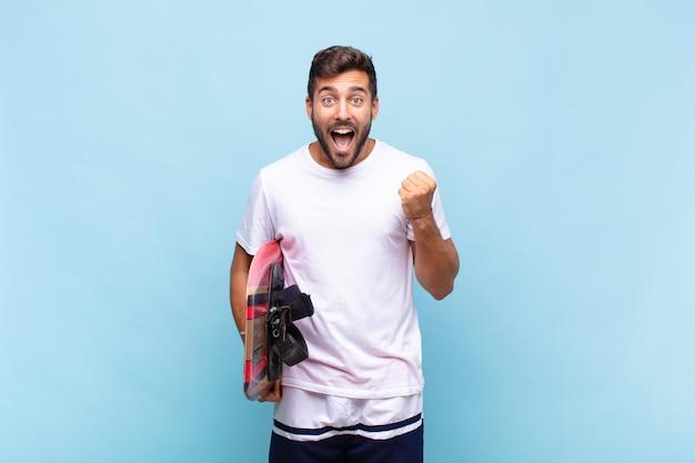 若い男はショックを受け、興奮し、幸せを感じ、笑い、成功を祝う